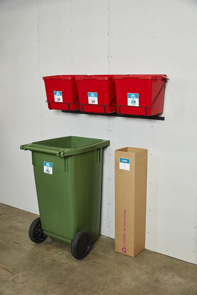 Tre röda boxar, ett kärl och en papperskartong för elavfall