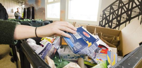 Kvinna som slänger pappersförpackning i ett soprum