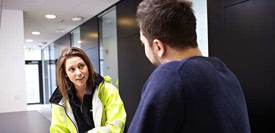En kvinna och en man samtalar på ett kontor